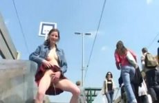 Halfnaakt meiske staat te pissen in het openbaar